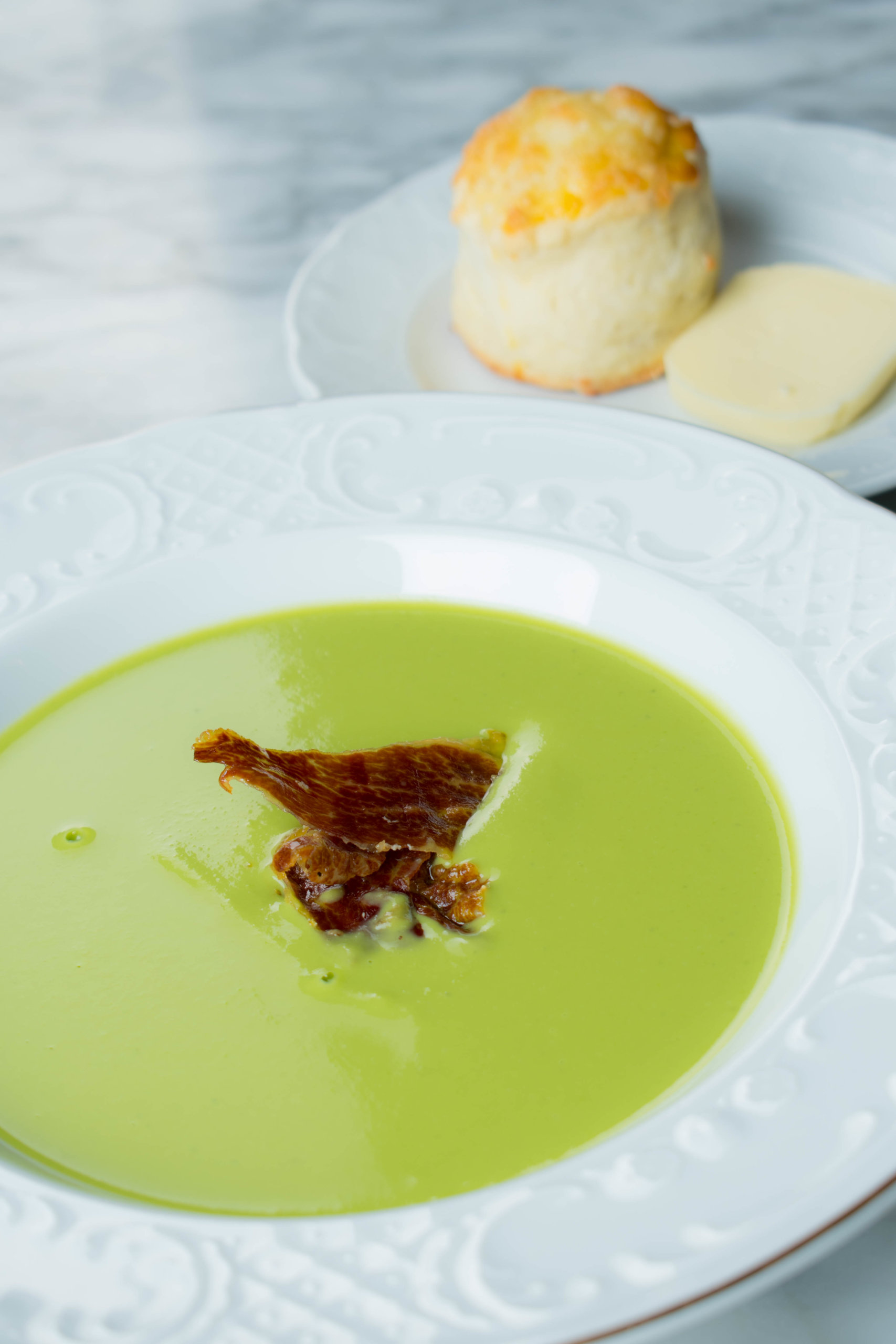「綠義漫遊 遠眺英倫」以醇香酥脆的伊比利黑毛豬火腿帶出翠綠青豆濃湯的清新, 配以英國傳統司康鬆餅,各款口感交錯出不同的層次。