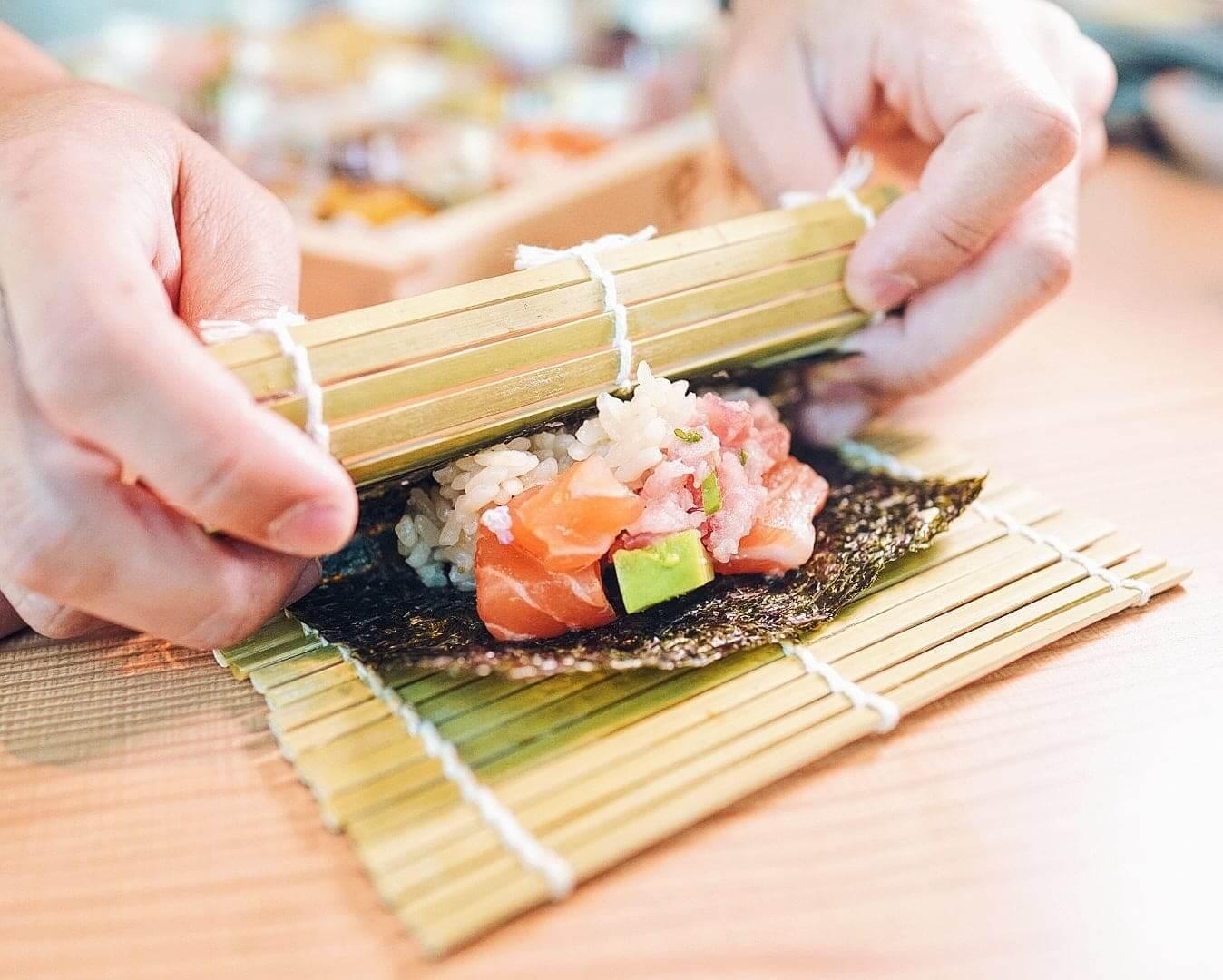 加上紫菜及精米飯,用竹簾卷壓。