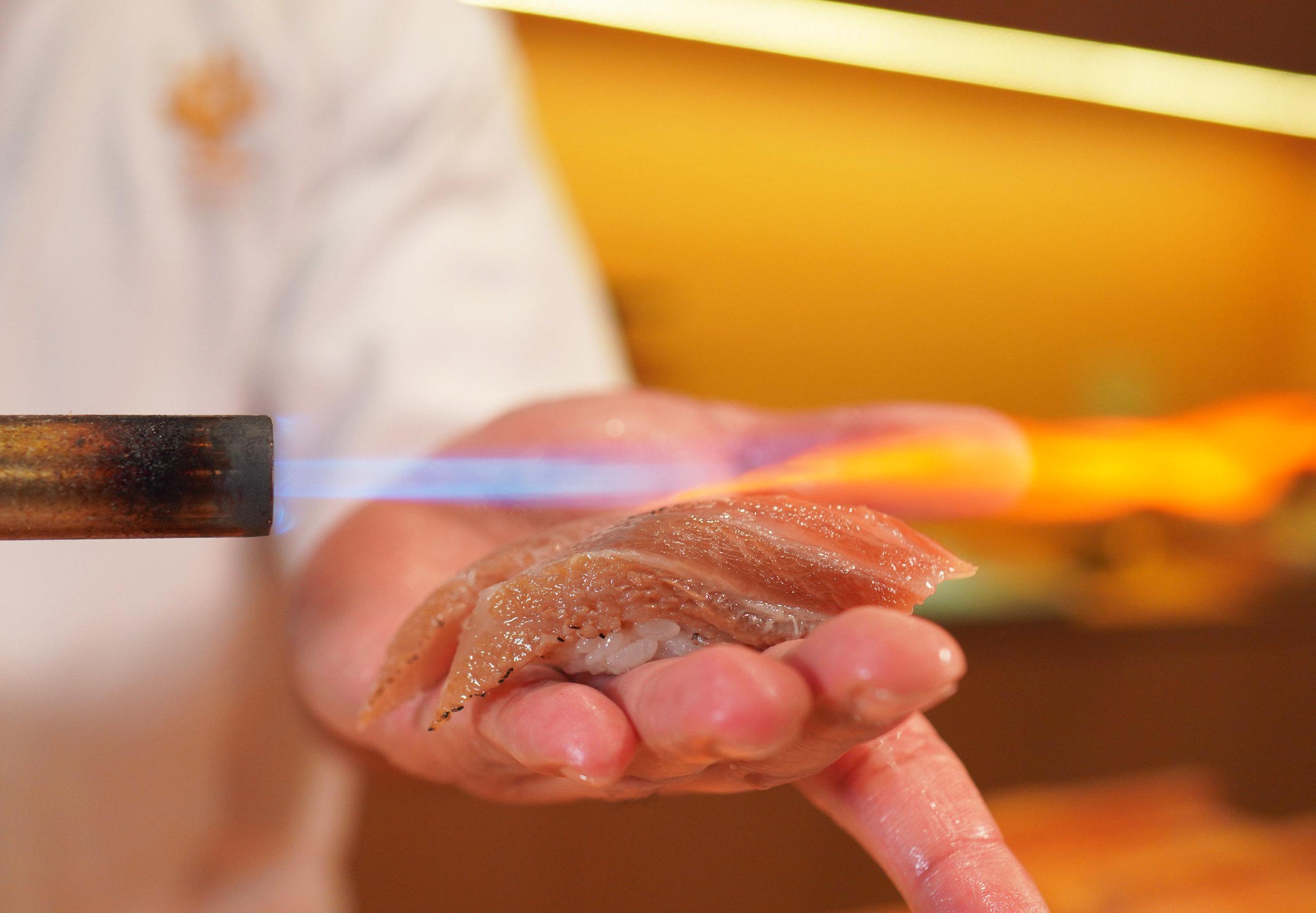 師傅將大拖羅壽司放在手掌上炙燒,功夫神乎其技。